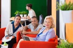Hommes d'affaires se tenant au compteur de réception Photographie stock libre de droits