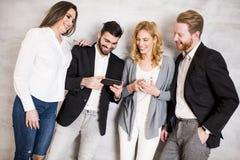 Hommes d'affaires se tenant contre le mur et employant leur mobile Photographie stock libre de droits