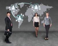 Hommes d'affaires se tenant devant une carte de la terre Image stock