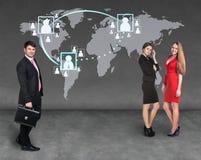 Hommes d'affaires se tenant devant une carte de la terre Photographie stock libre de droits