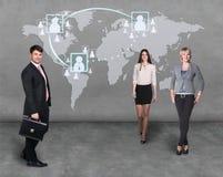 Hommes d'affaires se tenant devant une carte de la terre Photo libre de droits