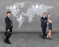 Hommes d'affaires se tenant devant une carte de la terre Photo stock