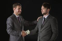 Hommes d'affaires serrant la main aux billets de banque du dollar images stock
