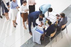Hommes d'affaires signant à la table d'enregistrement de conférence image stock