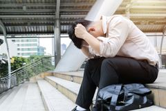 Hommes d'affaires soumis à une contrainte du travail tout en se reposant dehors sur le sta photo libre de droits