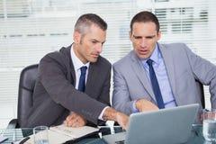 Hommes d'affaires sérieux travaillant sur leur ordinateur portable Image libre de droits