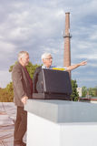 Hommes d'affaires supérieurs discutant des affaires sur le toit d'un bâtiment Images stock