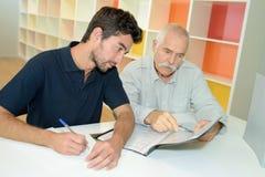 Hommes d'affaires supérieurs et jeunes discutant à la table ensemble Photographie stock libre de droits