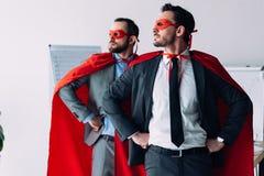 hommes d'affaires superbes beaux dans les masques et caps se tenant avec des mains sur les hanches photo stock