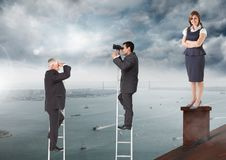 Hommes d'affaires sur des échelles au-dessous de la femme d'affaires se tenant sur le toit avec la cheminée et le port nuageux de photos stock