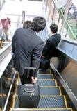 Hommes d'affaires sur l'escalier mobile photographie stock