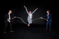 Hommes d'affaires tenant la corde tandis que sauter asiatique aux pieds nus mûr de femme d'affaires photos libres de droits