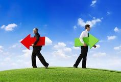 Hommes d'affaires tenant les flèches contrastantes Images stock