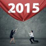 Hommes d'affaires tirant le numéro 2015 pour le progrès Image libre de droits