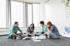 Hommes d'affaires travaillant au plancher à l'espace de travail créatif Image libre de droits