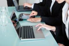 Hommes d'affaires travaillant aux ordinateurs portables et aux comprimés Photos stock