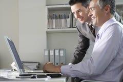 Hommes d'affaires utilisant l'ordinateur portable au bureau photos stock