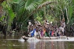 Hommes d'Asmat barbotant dans leur canoë de pirogue Photographie stock libre de droits