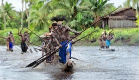 Hommes d'Asmat barbotant dans leur canoë de pirogue Images libres de droits