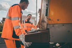 Hommes d'enlèvement de déchets travaillant pour un service collectif  photo libre de droits
