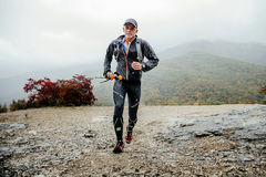 Hommes d'une cinquantaine d'années de coureur courant sous la pluie sur une traînée de montagne avec les poteaux de marche Photographie stock