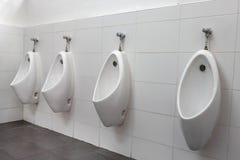 Hommes d'urinoirs dans les toilettes publiques Photo stock