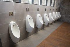 Hommes d'urinoirs publics dans la chambre de toilette Photo stock