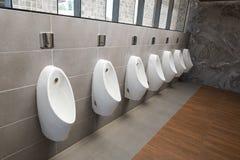 Hommes d'urinoirs publics dans la chambre de toilette Images stock