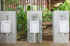 Hommes d'urinoirs publics dans la chambre de toilette, carte de travail Photos libres de droits