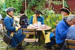 Hommes dans des costumes de cru parlant à la table images stock