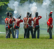 Hommes dans des manteaux rouges mettant le feu à des mousquets Photo stock