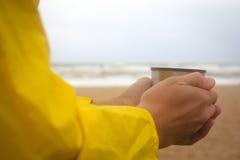 Hommes dans l'imperméable jaune sur la plage au-dessus de la mer orageuse tenant une tasse de thé chaud photo libre de droits