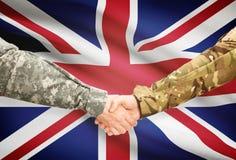 Hommes dans l'uniforme serrant la main au drapeau sur le fond - Royaume-Uni Photos stock