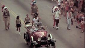 Hommes dans la voiture de vintage ondulant vers des spectateurs pendant le défilé banque de vidéos