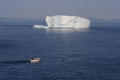 Hommes dans le bateau près des icebergs Photo libre de droits