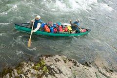 Hommes dans le canoë surchargé sur la rapide d'Alaska de rivière Photo libre de droits