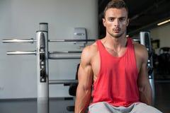 Hommes dans le gymnase exerçant le biceps avec des haltères Images stock
