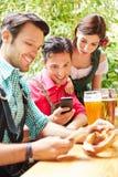 Hommes dans le jardin de bière regardant leur Photo libre de droits