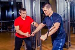 Hommes de aide d'entraîneur personnel établissant dans la chambre de poids au gymnase Photo stock