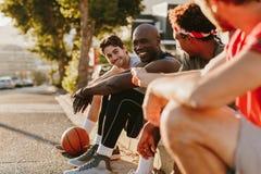 Hommes de basket-ball s'asseyant sur le trottoir et parler Image libre de droits
