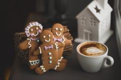 Hommes de biscuit de pain d'épice dans une tasse chaude de cappuccino Image stock