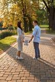 Hommes de couples de famille et une jeune femme enceinte marchant tenant le jouet d'ours de nounours en parc photo stock