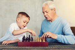 Hommes de deux générations jouant des échecs ensemble Photographie stock libre de droits