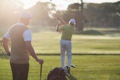 Hommes de golfeur se tenant sur le champ Images stock
