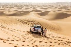 Hommes de guide de voyage avec la voiture d'entraînement à quatre roues sur le grand désert chez Dubaï Photographie stock