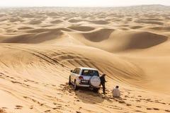 Hommes de guide de voyage avec la voiture d'entraînement à quatre roues sur le grand désert chez Dubaï Image libre de droits