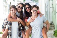 Hommes de hanche donnant sur le dos à leurs amies Photos libres de droits