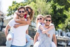Hommes de hanche donnant sur le dos à leurs amies Photo stock
