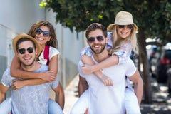 Hommes de hanche donnant sur le dos à leurs amies Photos stock