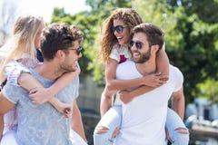 Hommes de hanche donnant sur le dos à leurs amies Photographie stock libre de droits